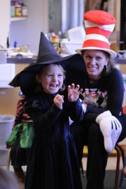 Averill Hollond, 3, a preschooler at the Lawrence Arts Center, 940 N.H., tries to scare classmates Thursday with the help of Megan Hay, a teacher dressed like the Cat in the Hat.