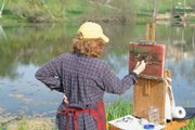 "Mary Binford Miller, of El Dorado, paints a scene at Kansas University&squot;s Potter Lake. Miller is one of 63 artists exhibiting in ""A Spring Day on the Hill"" at SouthWind Gallery in Topeka."