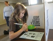 Avianna Myers-Arenth, 7, makes her choice for president in a Kids Voting booth at the Union Pacific Depot and Visitors Center Tuesday. Voters across the nation were deciding on several local issues as well as for several state and national congressional offices. In background at left is Avianna's mother Alison Myers-Arenth who also voted Tuesday.