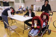 At right, Shawn Alexander and his wife Kelly Farrell, along with their 16-month-old twins Francis Alexander, foreground, and Leigham Alexander, vote at New York School on Tuesday.