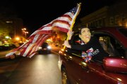 An Obama supporter, hidden by a mask resembling the to-be President, waves a flag while hanging out of an SUV window shortly after midnight early Wednesday morning after Barack Obama elected the 44th president of the United States.