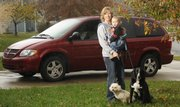"Lori Kemme, Lawrence, used to drive a sports car like her husband, Scott. But when the Kemmes were planning on the birth of their son, Lori traded in her car for a new ""mom vehicle,"" the Dodge Grand Caravan. Now, Lori and Scott have a vehicle for the whole family, including their two dogs. Kemme is picture with her 14-month-old son, Ronan, and dogs Bennie, left, and Toby."