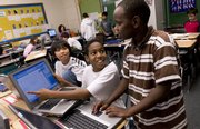 Hillcrest School sixth-graders, from left, Jay Xayasaeng, of Laos, Sebastian Joseph and Alex Mwithiga, of Kenya, work through transformational geometry Thursday at the school, 1045 Hilltop Drive. Many international students make up the student body.