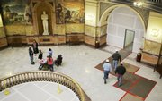 A tour of the Statehouse goes on Friday while workers enter a construction area off the rotunda in Topeka. Despite rising costs and a strained budget, Statehouse renovations continue.