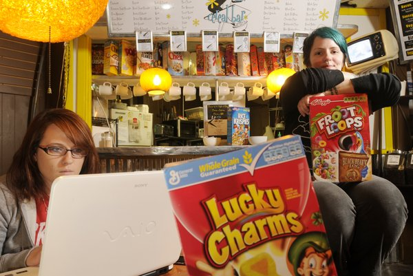 Brenna McKedy, a Kansas University junior from Garden City, left, works on homework near the cereal bar at Java Break, 17 E. Seventh St. Sarina Geist, right, store manager, says cereal bars are popular on the coasts and suit Java Break's college-age clientele.
