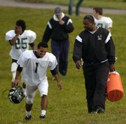 Jesse Brinson chats with Free State High School junior quarterback Camren Torneden on the way to the practice fields. Brinson came to Kansas University in 1999 and walked on the football team as a fullback and linebacker. He is heading up the Night of Heroes, which will feature former NFL player Scott Turner.