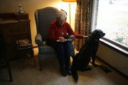 Marion Willey, of Lawrence, finds company in a good read and her dog, Dena, recently in her south Lawrence home. Willey, an avid reader, believes reading helps calm her and benefits her health.