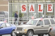 A car salesman paces outside the used car lot on Thursday, Nov. 13, 2008 at Jim Clark Motors, 2121 W. 29th Terrace.  The economy has created hardship for car dealerships and bargains for car buyers.