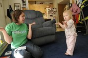 Brooke Theisen, left, works with her 16-month-old daughter Madison on learning sign language. Although a few of the signs are known only by Madison and her parents, she is learning many American Sign Language gestures for words like mother, father, dog, more and hungry.