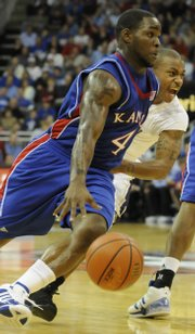 Kansas guard Sherron Collins drives against Washington guard Isaiah Thomas during the first half of the CBE Classic Monday, Nov. 24, 2008 at the Sprint Center in Kansas City, Mo.