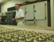 Mike Tennyson, owner of Munchers Bakery, 925 Iowa, prepares mini cinnamon rolls to be fried on Saturday night. Munchers is the only 24-hour bakery left in Lawrence, and Tennyson said he produced thousands of pastries on a nightly basis.