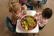 A bowl of vegetables awaiting attention sits on a table between Raintree students.