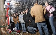 Friends of 19-year-old Casey Alan Anzek gather Monday at the site of a car accident that happened early Saturday morning in the 2500 block of Ousdahl Road that killed Anzek and injured four passengers. The tree hit by the car has become a memorial site where those gathered recalled stories about Anzek.