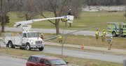 Workers from Westar Energy along with Lawrence Douglas County Fire and Medical remove a light pole around 9:45 a.m in the eastbound lane of Clinton Parkway just west of Iowa Street on Wednesday.