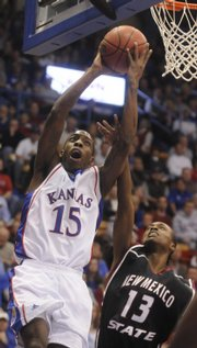 Kansas guard Tyshawn Taylor elevates to the bucket over New Mexico State Laroche Hernst during the first half Wednesday, Dec. 3, 2008 at Allen Fieldhouse.