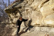 Kelly Kindscher, secretary on the Kansas Land Trust board of directors and a plant ecologist with the Kansas Biological Survey, looks for names etched in the 40-foot sandstone bluff along Coal Creek in Baldwin Woods.