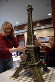 Jean Robinson, Lawrence, left, is assisted by Cyndia Dorathy, member of the gingerbread committee, Dec. 6, 2008, as Robinson puts together her gingerbread Eiffel Tower. Artists of all ages and abilities contribute gingerbread houses for the auction.