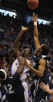 Kansas guard Tyshawn Taylor lofts a shot between Jackson State defenders Darrion Griffin (12) and Grant Maxey (32) during the first half Saturday, Dec. 6, 2008 at Allen Fieldhouse.