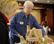 Cyndia Dorathy, member of the Gingerbread Committee, left, and Keith Wood, executive director of Big Brothers Big Sisters of Douglas County, set up gingerbread houses Saturday at The Eldridge Extended, 201 W. Eighth St. Wood has signed up to be executive director of the Douglas County agency and is working to raise the organization's profile.