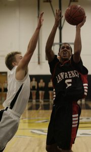 Lawrence High's Marcus Ray drives the lane for a basket over Blue Valley High's Josh Wormington during the second half of Friday night's game at Blue Valley High School, Dec. 12, 2008.