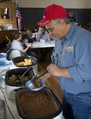 John Rodecap fills his plate during his welcome-back dinner Saturday afternoon at at Buck Creek School, near U.S. Highway 24 in Jefferson County. John returned from duty last week.