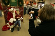 Santa, also known as Larry Freeman, chats with Joseph Rice, 3, as Joseph's mother, Kelly Rice, snaps a photo with a digital camera Saturday afternoon at Weaver's Department Store in downtown Lawrence. Freeman says that he loves all kinds of cookies underneath the Christmas tree, and that there is no such thing as a bad cookie.