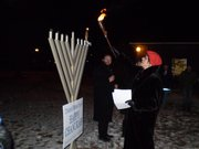 Leni Salkind lights a giant menorah outside the South Park Recreation Center on the first night of Hanukkah. In back is Rabbi Zalman Tiechtel of the KU Chabad Center for Jewish Life.