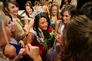 Alexis Rewalt, center, laughs with other contestants in the Miss Kansas Teen USA competition after winning the crown Sunday night in the Lied Center.
