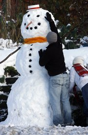 """Jeff Olson puts the finishing touches on an 8-foot snowman built by him and his girlfriend, Veronica Nim, in front of Nim's house in West Seattle. """"It's not the biggest one we've done,"""" Olson said, recalling a 15-footer he built with the help of a football team several years back. Heavy snowfall and sub-zero temperatures are causing big problems across the U.S."""