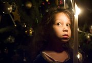 Sofia Thomas, 5, holds a candle during a Christmas tree lighting ritual at a holiday party Sunday at the residence of Serina Hearn and Tony Backus, 1941 Mass.