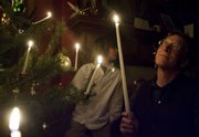 Tony Backus helps children light candles during a party at his home on Massachusetts Street.