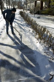 Steve Ellsworth clears snow Wednesday from the sidewalk in front of his home along Massachusetts Street. Lawrence residents now face a new city ordinance that requires home owners to clear snow and ice off sidewalks within 48 hours or risk getting a ticket. The new rule eliminates the former five-day grace period.