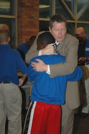 FORMER KU FOOTBALL COACH MIKE GOTTFRIED hugs a camper in Mobile, Ala. Gottfried founded Team Focus, a program aimed at providing guidance to kids growing up without fathers.