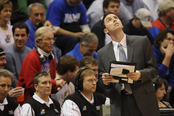 Former Jayhawk guard and current director of basketball operations Brett Ballard checks the scoreboard during a timeout in this Dec. 20 file photo from Allen Fieldhouse.