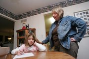 Gretchen Boxberger, 10, gets help with her homework from her mother, Sheri, in the early evening before dinner. Sheri and her husband, Tom, make a point of interacting with their children in their home each night. 