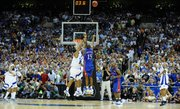 Kansas guard Mario Chalmers hoists a three-pointer over Memphis guard Derek Rose with seconds remaining in the second half of the national championship Monday, April 7, 2008, at the Alamodome in San Antonio.