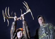 Chad Christie, right, of Baldwin city, shot a large buck within a quarter-mile of his house in early December. The 20-point buck will probably be recorded as one of the biggest ones ever shot in the state. Christie's son Justin, 10, holds up the antlers outside their house on Dec. 17.
