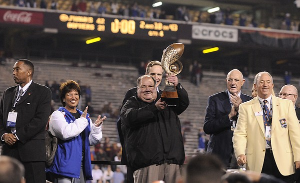 Kansas head football coach Mark Mangino hoists the Insight Bowl trophy following the Jayhawks' 42-21 win over Minnesota Wednesday, Dec. 31, 2008, at Sun Devil Stadium in Tempe, Arizona.