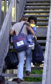 Latina Alston carries several bags filled with law books and her young son Malcolm up the stairs to their second-floor apartment in Topeka on Sept. 15.
