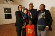 Latina Alston, left, stands with her family in their new home in Wichita on Dec. 18. Latina is holding Dylan, 1. At center is Tia, 11. Latina's mother, Dee Alston, is on the right. Standing below is Malcolm, 5.