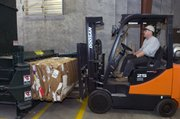 Tom Boxberger uses a forklift to remove packed bundles of cardboard from the compactor Friday at the KU recycling center.