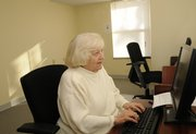 Alice Murphy, a resident of Clinton place Apartments, types an e-mail on one of two computers in the complex's activity room.
