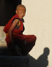 a 13-year-old monk sits perched on a step outside his Ganden Sumtseling Monastery dwelling. Kids as young as 6 or 7 come to the monastery to study how to become a monk.