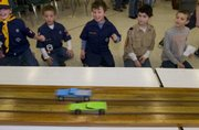 Young fans Nicholas Guerrero (from left), Will Damron, Justin Miller Max Briggs and Devin Duncin watch as the final cars come in a close finish. Cub Scouts with Pack 3071 held their pinewood derby race Saturday at Prairie Park School in Lawrence.