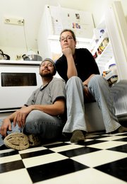 "Josh ""Yosh"" James, 30, and Meredith Trewolla are pictured in front of the refrigerator in their apartment. The couple decorate their fridge with a variety of magnets and lists, but a particularly enticing feature is their erotic wordplay magnets that entertain their friends."