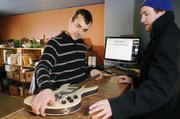 Sean Passmore, owner of Bling Drop-off Store, looks at a guitar brought in by KU student Dave Clothier. Passmore hopes his start-up business will make it through the recent economic recession. Passmore will try to sell Clothier's guitar on eBay.