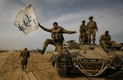 An Israeli soldier jumps off an armored vehicle carrying a flag of Israel&#39;s 60th anniversary as he celebrates with his unit their return from the Gaza Strip on the Israeli side of the border, Friday Jan. 16, 2009. Top Israeli diplomats headed for Egypt and the United States on Friday in what appeared to be a final push toward a cease-fire to end Israel&#39;s punishing Gaza offensive against Hamas militants. 
