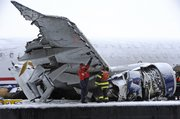 The badly damaged wing and engine of the US Airways Airbus A320 is inspected out of the water on a barge, Sunday, Jan. 18, 2009, in New York. Workers plan to remove the plane during the day to an undisclosed location.