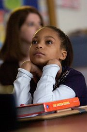 Fifth-grader Marcya Floyd leans on her history book while she watching the swearing in of President Barack Obama in her classroom at New York Elementary School on Tuesday.