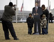 Billy Johnson, far left, of Charlotte, N.C., photographs General Mealer, right, with his grandsons Daryll Mealer, 7, second from left, and Jason Mealer, 6, with a cardboard cutout of President-elect Barack Obama on the National Mall in Washington, Monday, Jan. 19, 2009. The Mealers are from Carry, N.C.